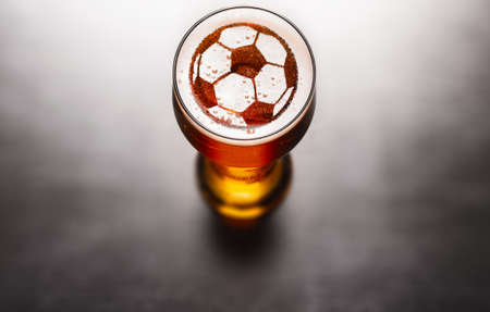 Sports bar beer concept. Soccer of football ball symbol on beer glass foam on black table, view from above