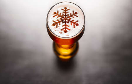 Christmas or New Year beer concept. Snow symbol on beer glass foam on black table, view from above Stock Photo