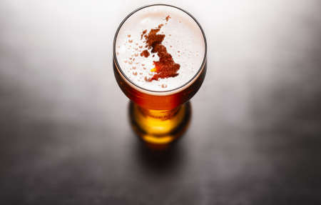English beer concept, Great Britain silhouette on foam in beer glass on black table. Elements of this image furnished