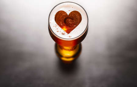Liebevolles Bierkonzept. Herzsymbol auf Bierglasschaum auf schwarzem Tisch, Ansicht von oben Standard-Bild