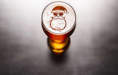 Christmas or New Year beer concept. Star symbol on beer glass foam on black table, view from above Stockfoto