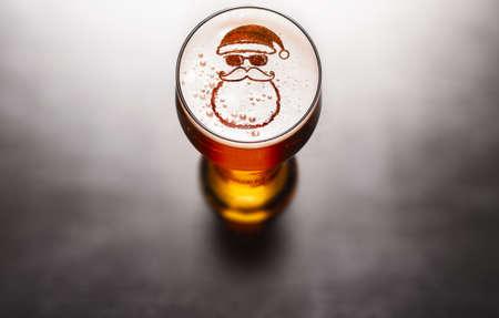 Concetto di birra di Natale o Capodanno. Simbolo della stella sulla schiuma del bicchiere di birra sul tavolo nero, vista dall'alto Archivio Fotografico