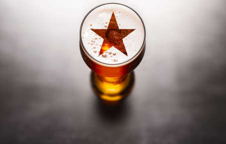 Famous beer concept. Star symbol on beer glass foam on black table, view from above