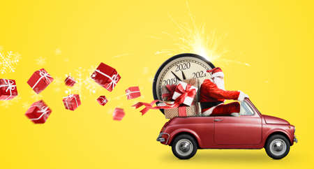 Christmas countdown arriving. Santa Claus on snowy toy car delivering New Year gifts and clock at yellow background Stock Photo