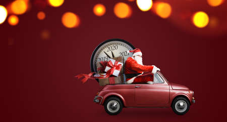 Christmas countdown arriving. Santa Claus on car delivering New Year gifts and clock at red background Standard-Bild