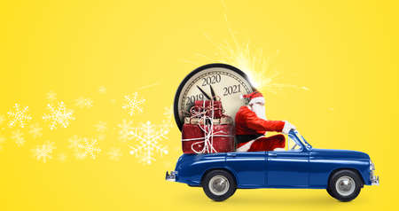 Christmas countdown arriving. Santa Claus on snowy toy car delivering New Year gifts and clock at yellow background Stockfoto - 130060140