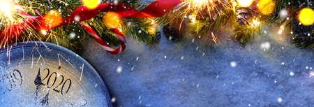 真夜中にカウントダウン。クリスマスまたは新年2020の前に最後の瞬間を数えるレトロなスタイルの時計は、装飾されたモミの木の隣に。上から見る