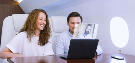 Making video conference call with colleague on laptop HUD hologram on board of private jet. Caucasian businessman and businesswoman travel inside of business airplane cabin. 写真素材
