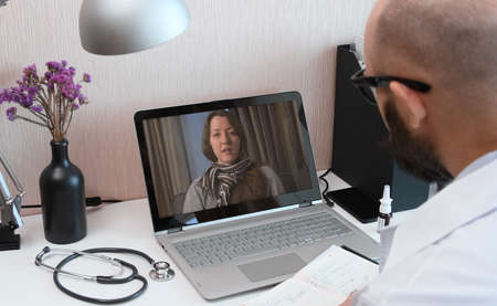 Telemedicine. Consultation with physician through mobile video call. Doctor talking to comlaining patient using video chat application on laptop and writes down symptoms.