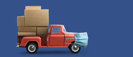 Safe delivery. Toy car in mask delivering blank boxes. Loaded red pickup truck with protection on blue background
