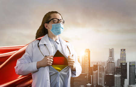 Medical superhero showing flag of Germany. Heroic doctor wearing mask and red cape fighting with epidemic in city. Young woman. Brave medical staff concept.