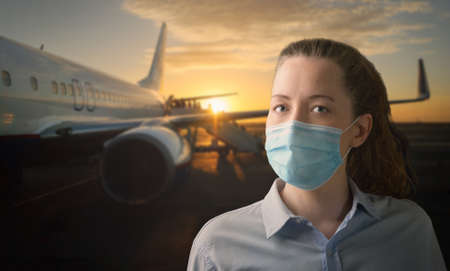 Face mask on board. Woman wearing medical mask while boarding airplane at airport. Passengers required to wear facial protection during flight. Imagens