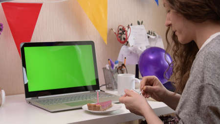 Woman celebrating her birthday through video call virtual party. Lits and blows out candle. Authentic decorated home workplace. Handheld shot with gimbal. Coronavirus outbreak 2020. Imagens