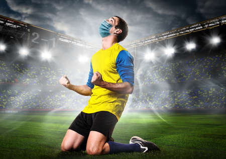 Soccer or football player wearing mask. Team sports player in medical mask emotionally kneel on stadium during coronavirus outbreak. Archivio Fotografico