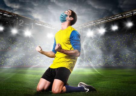 Joueur de football ou de football portant un masque. Un joueur de sport d'équipe portant un masque médical s'agenouille émotionnellement sur le stade lors d'une épidémie de coronavirus. Banque d'images