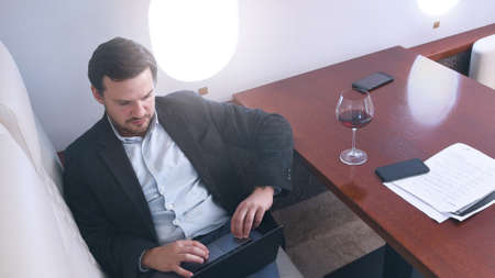 Business man working comfortably on laptop on board of private jet. Caucasian businessman travel inside of business airplane cabinwith glass of wine, view from above.