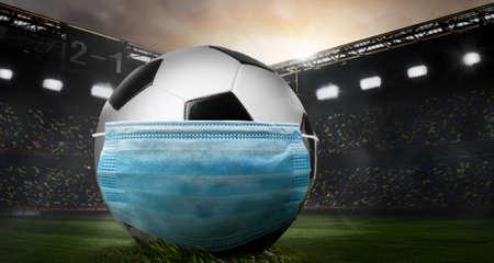 Play safe. Soccer or football ball wearing mask on stadium during coronavirus outbreak.