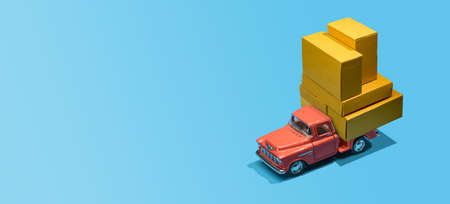Fast order delivery by car concept. Pickup truck delivering blank boxes. Loaded retro toy car loaded with cardboard packages isolated on blue background. Imagens