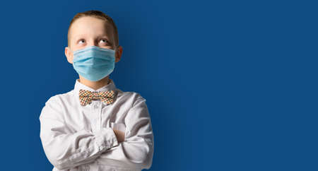 School boy wearing face mask standing against blackboard. Safe back to school during pandemic concept. New normal education. Hands folded and looking upwards
