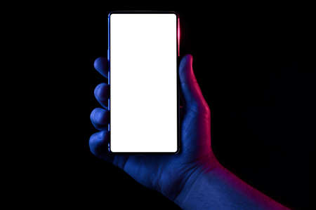 Phone in hand. Silhouette of male hand lit with blue and red neon lights holding bezel-less smartphone on black background. Screen is cut with clipping path. Imagens