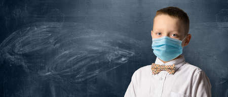 School boy wearing face mask standing against blackboard. Safe back to school during pandemic concept. New normal education.