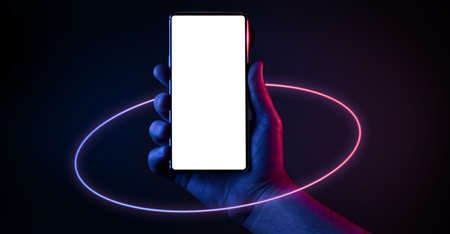 Phone in hand. Silhouette of male hand holding bezel-less smartphone with futuristic neon light circle on dark background. Screen is cut with clipping path. Imagens