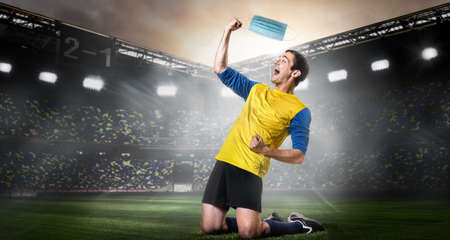 Soccer or football player removing mask. Team sports player taking off medical mask and happily kneel on stadium. End of coronavirus outbreak. Imagens