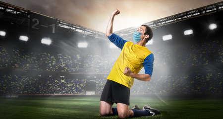 Soccer or football player wearing mask. Team sports player in medical mask emotionally kneel on stadium during coronavirus outbreak. Imagens