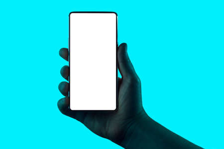 Hand holding phone. Silhouette of male hand holding smartphone isolated on aqua blue background.