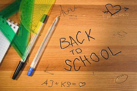 Back to school writing on wooden desk. Top view of school table with supplies and accessories. Shadow and sun beam overlay.