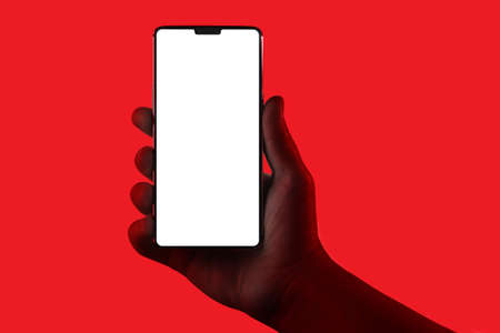 Hand holding phone. Silhouette of male hand holding smartphone isolated on red background.