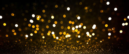 Abstract blurred background, yellow lights on black background. Golden christmas or new year bokeh. Defocused party night lights.