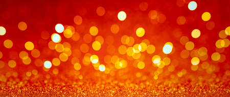 Abstract blurred background, yellow lights on red background. Golden christmas or new year bokeh.