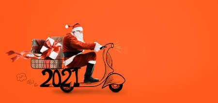Santa Claus on scooter delivering Christmas or New Year 2021 gifts at orange background Stock Photo