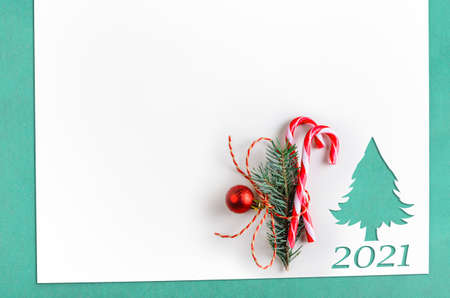 Christmas background. White paper with fir-tree shape cut for new year 2021 card on wooden table Archivio Fotografico