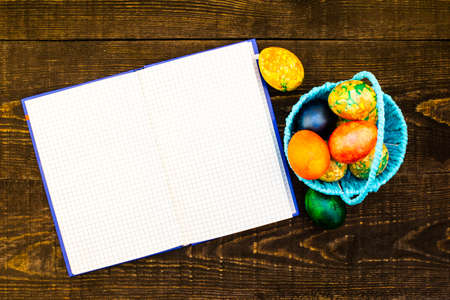 a blue basket with Easter eggs and the nearby Easter eggs on the dark brown wooden background, an expanded notebook for replicas of copy space