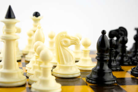 white chess pieces stand on a chessboard during a game of chess, focus in the center of the board