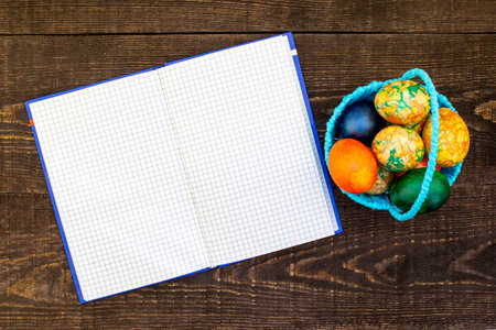 blue basket with Easter eggs on the dark brown wooden background, unfolded notebook for copy space Imagens