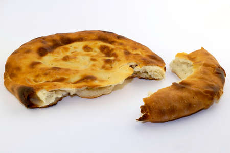 Caucasian unleavened white bread made from wheat flour - pita bread - on a white background, with a broken off piece 版權商用圖片