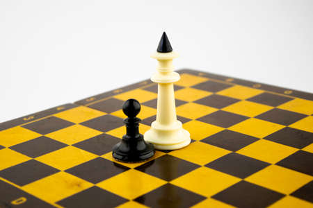 the white chess king and black pawn stand next to the chessboard