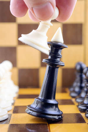 White pawn in the hand of the chess player beats the black king