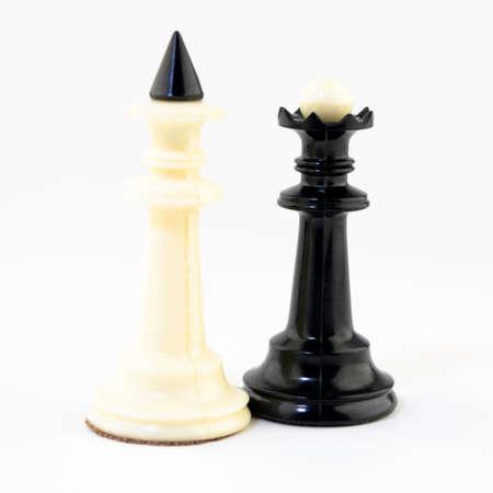 El rey de ajedrez blanco y la reina negra están de pie junto al fondo blanco.