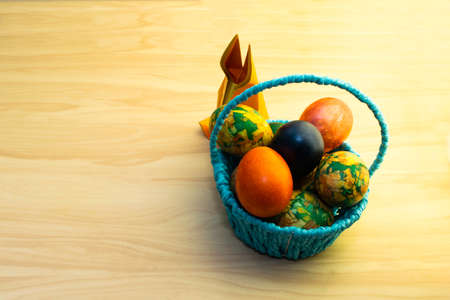 Easter eggs lying in the blue basket and a paper rabbit on a yellow wooden table, copy-paste