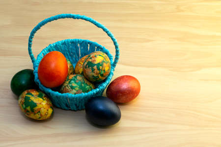 Easter eggs lying on the yellow wooden table and in a blue basket, copy pastes