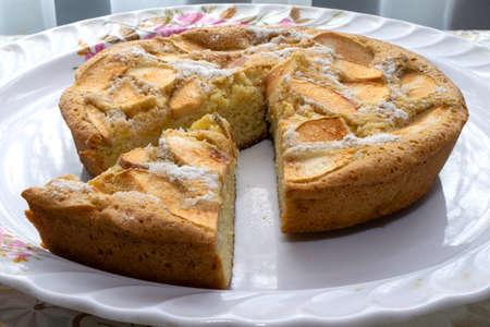 Pan di Spagna di cottura con mele, Charlotte, pan di spagna con mele e una fetta tagliata da esso