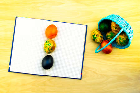 Easter eggs lying in the blue basket and on a yellow wooden table, a book for notes as a copy of pastes and eggs lying on it