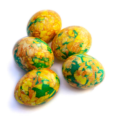Traditions. handmade yellow green easter eggs painted marbled over white background