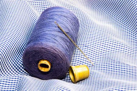reel of thread, needle and thimble on a piece of tartan Stockfoto