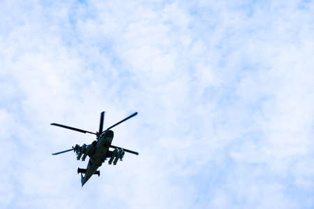 Russian military combat attack helicopter K-52 Alligator flies against the blue sky and clouds