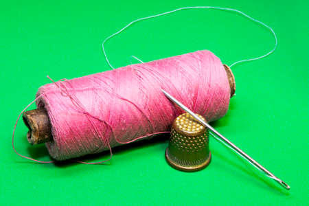 reel of pink thread, needle and thimble on a green background Stockfoto - 125216092